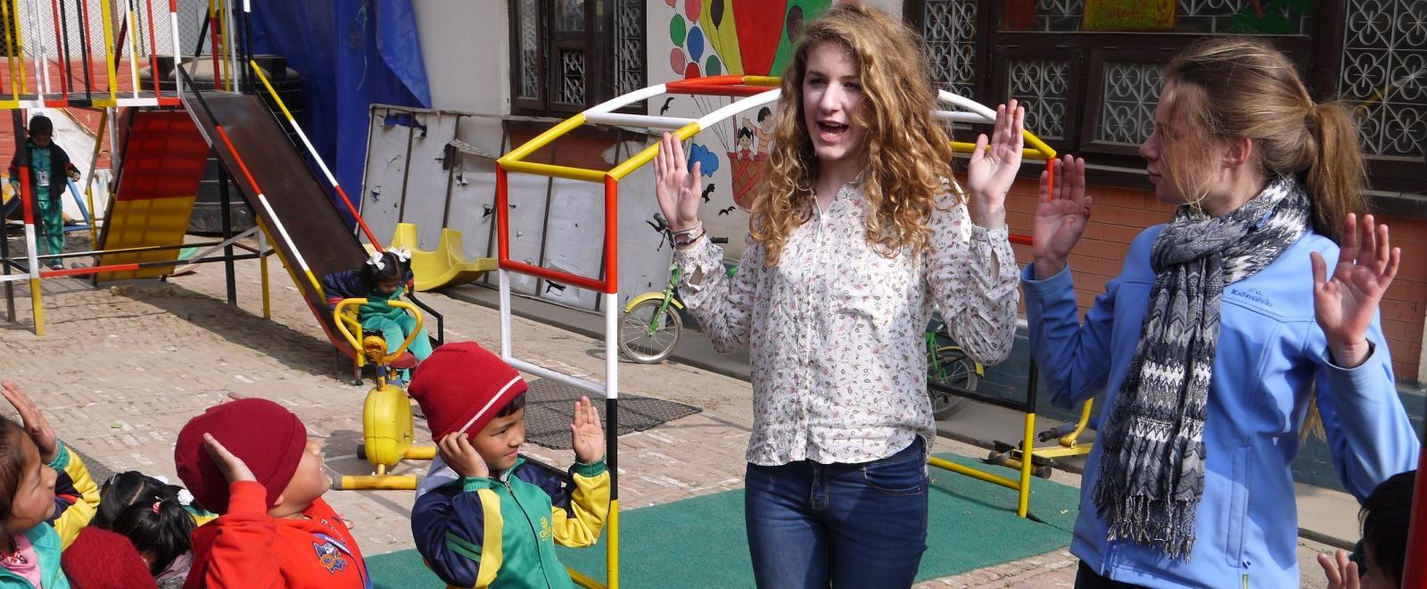 Teenage volunteers doing work with children in Nepal, do an activity with children on the playground.